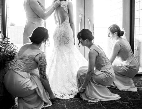 Bridesmaids adjusting Bride's Dress before ceremony BW