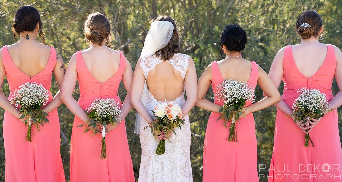 Wedding photography of bridesmaids holding flowers behind their backs.